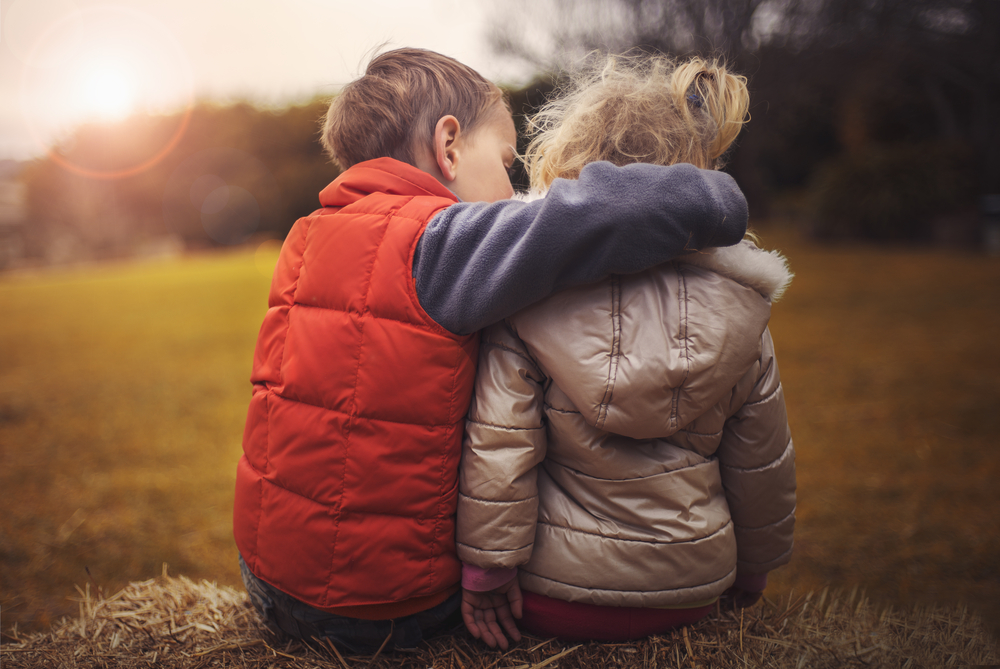 children hugging at sunset